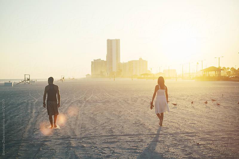 Couple walking on beach  by Borislav Zhuykov for Stocksy United