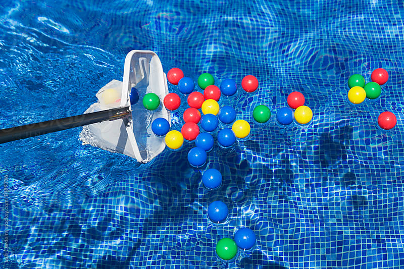 Color balls on a swimming pool by Luis Cerdeira for Stocksy United