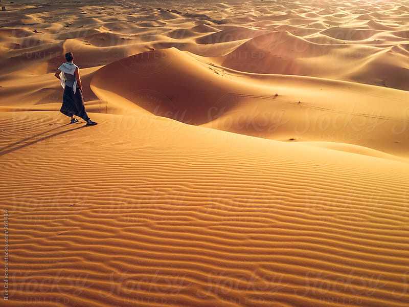 Young woman enjoying sunset on a desert dune landscape by Blue Collectors for Stocksy United