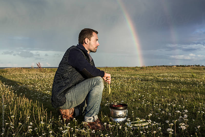 Rainbow over a man cooking in a field by Lior + Lone for Stocksy United