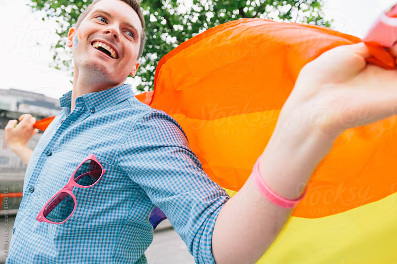 Happy Gay Man with a Rainbow Flag by HEX. for Stocksy United