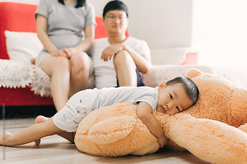 Cute toddler lying on his big Teddy with his parents in the background by MaaHoo Studio for Stocksy United