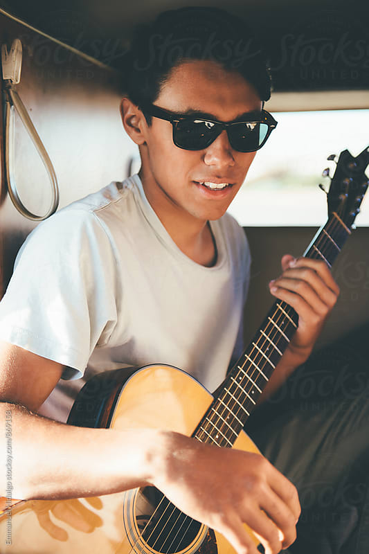 Young man holding his acoustic guitar in his classic VW bus by Emmanuel Hidalgo for Stocksy United
