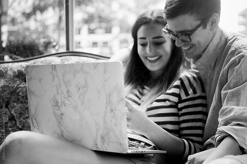 A young couple sitting at a cafe using a laptop and studying by Chelsea Victoria for Stocksy United