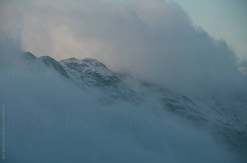 Cloud shrouding winter mountain summit by Neil Warburton for Stocksy United