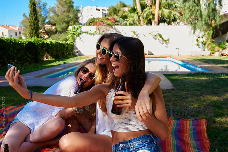 Girls taking selfie on backyard against of swimming pool by Guille Faingold for Stocksy United