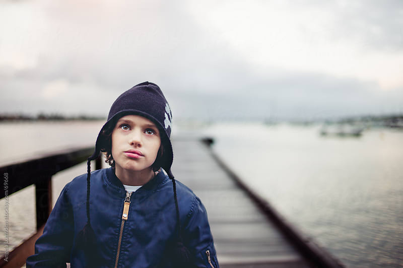 Boy on a dock in winter by Angela Lumsden for Stocksy United