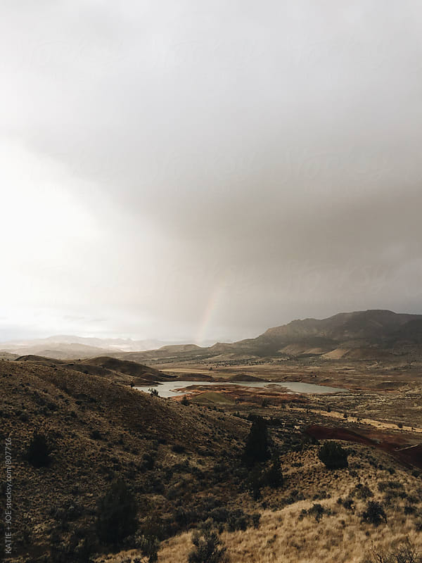 Rainbow in an overcast sky over the painted hills in oregon by KATIE + JOE for Stocksy United