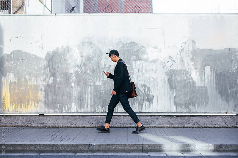 Stylish asian businessman using phone walking on the street.  by BONNINSTUDIO for Stocksy United