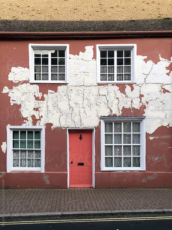 Old terraced house with peeling paint on the exterior. by Paul Phillips for Stocksy United