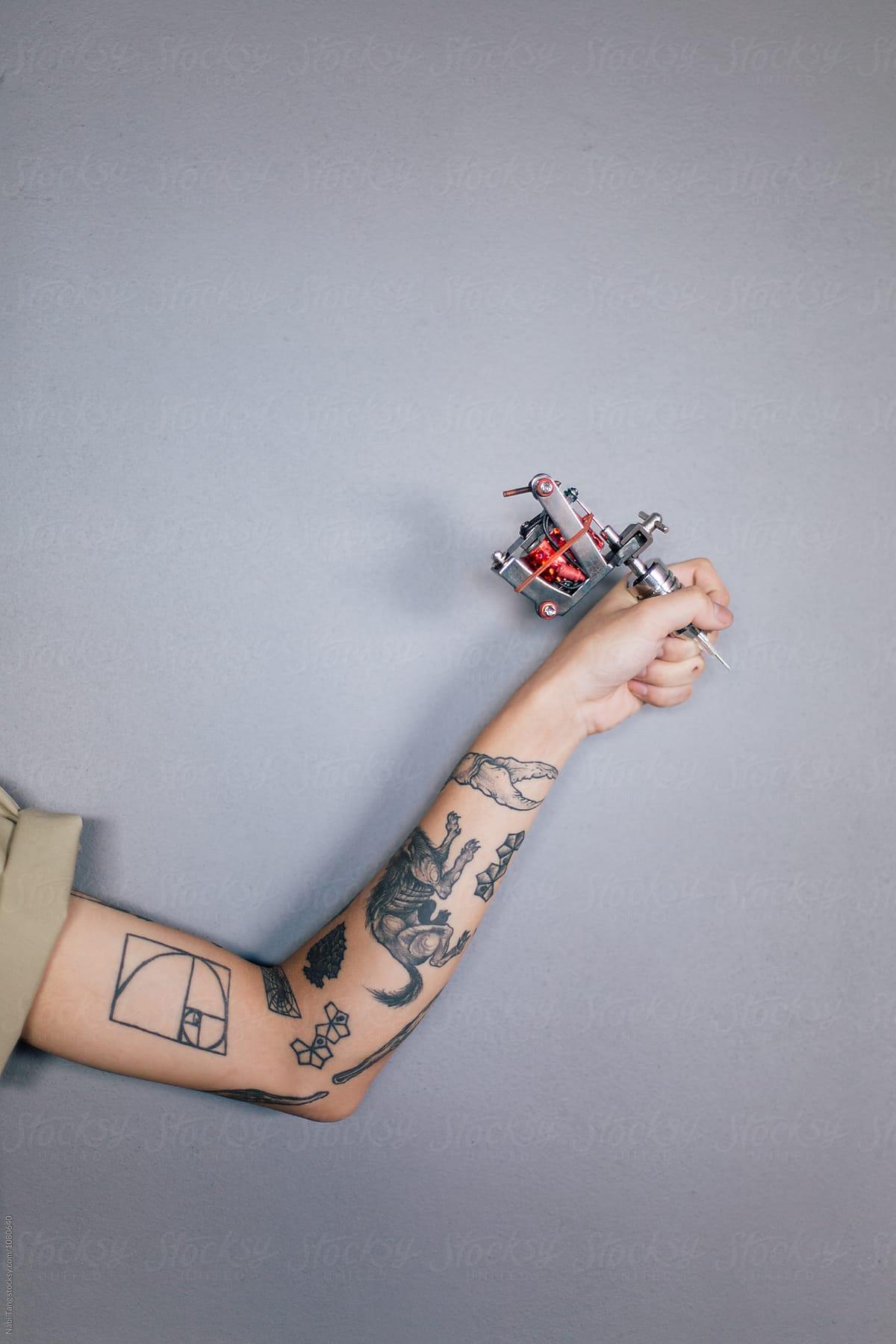 Artist Hand Holding Tattoo Gun