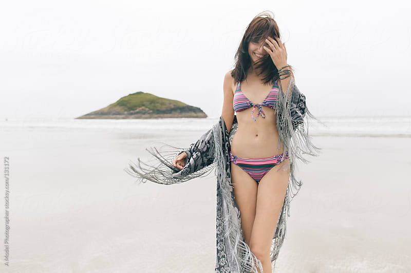 A woman standing on a beach hiding her face and laughing in a pink bikini by Ania Boniecka for Stocksy United