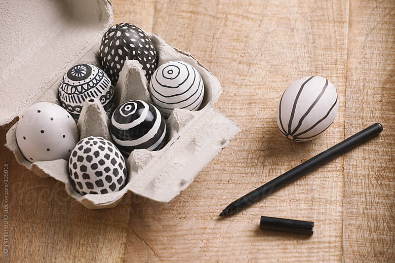 Easter eggs with different drawings on a egg-cup.  by BONNINSTUDIO for Stocksy United
