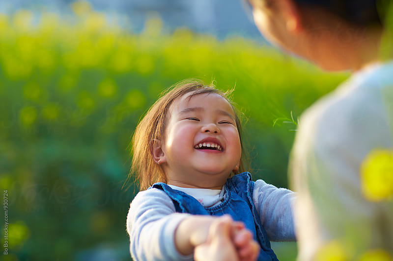happy little asian girl  having fun with her mother outdoor in the spring field by Bo Bo for Stocksy United