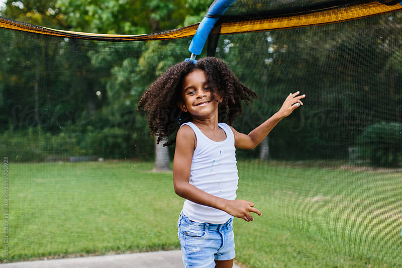 A little girl jumping on a trampoline with her hair down by Kristen Curette Hines for Stocksy United