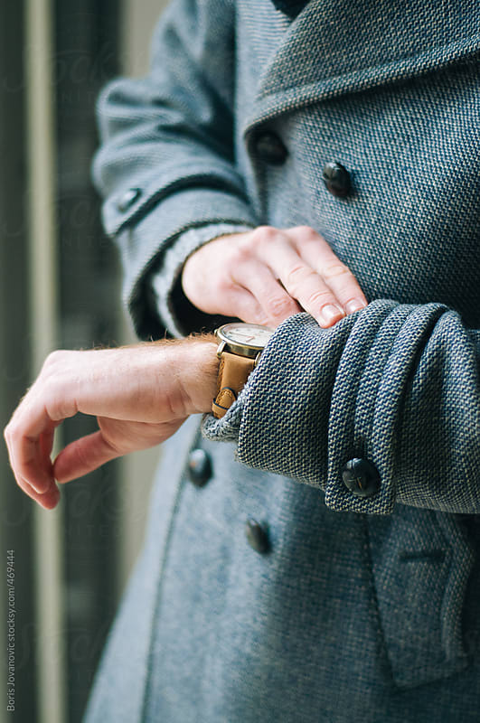 Young caucasian guy in coat looking at his watch by Boris Jovanovic for Stocksy United