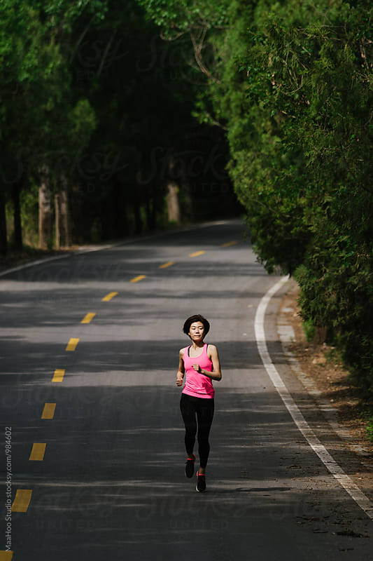 Young woman running on a road by Maa Hoo for Stocksy United