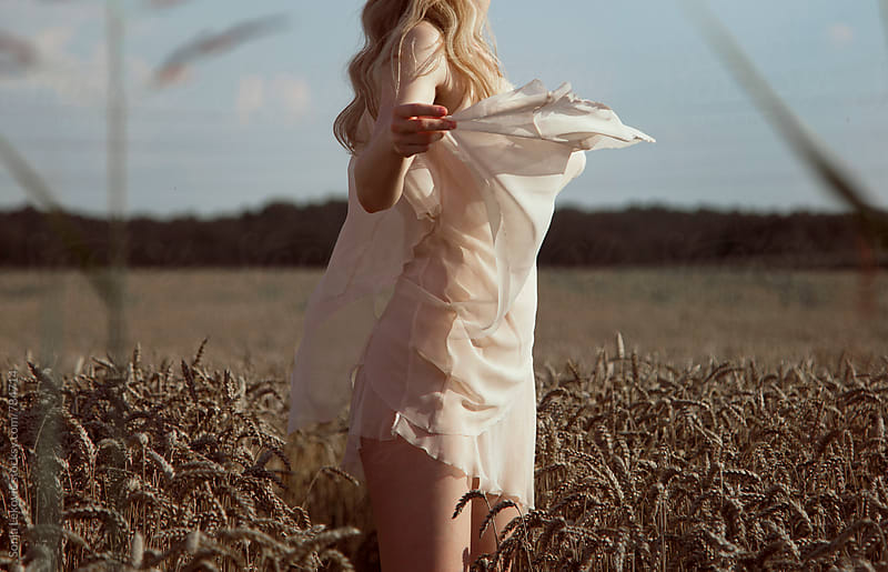 woman in transparent light dress in the field by Sonja Lekovic for Stocksy United