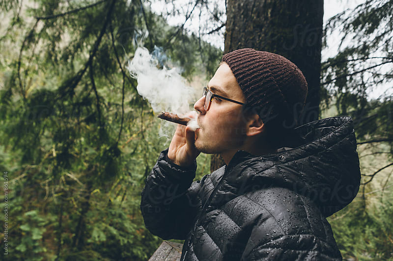 Young Man Smoking Cigar Outside In Forest Air by Luke Mattson for Stocksy United