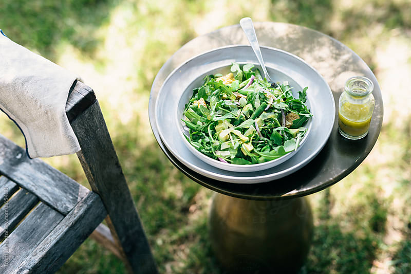 Plate of homemade salad and sauce on table in quiet outdoors by Trent Lanz for Stocksy United