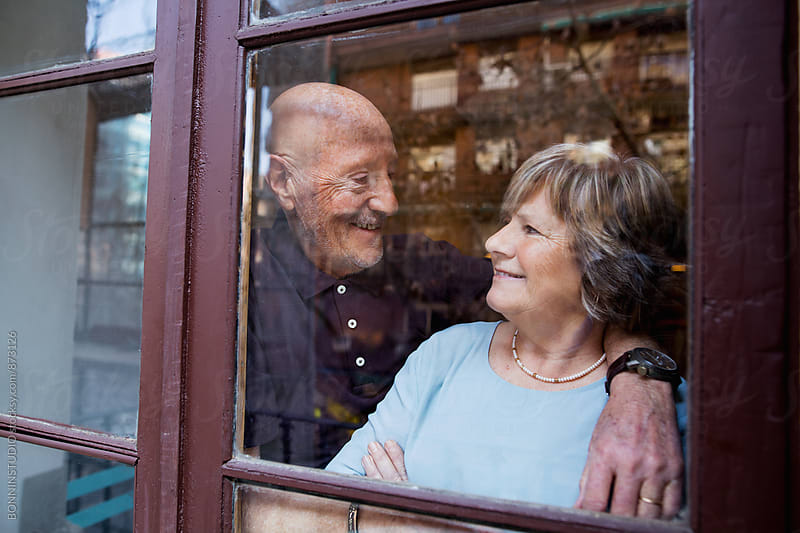 Elderly couple together standing through the window. by BONNINSTUDIO for Stocksy United
