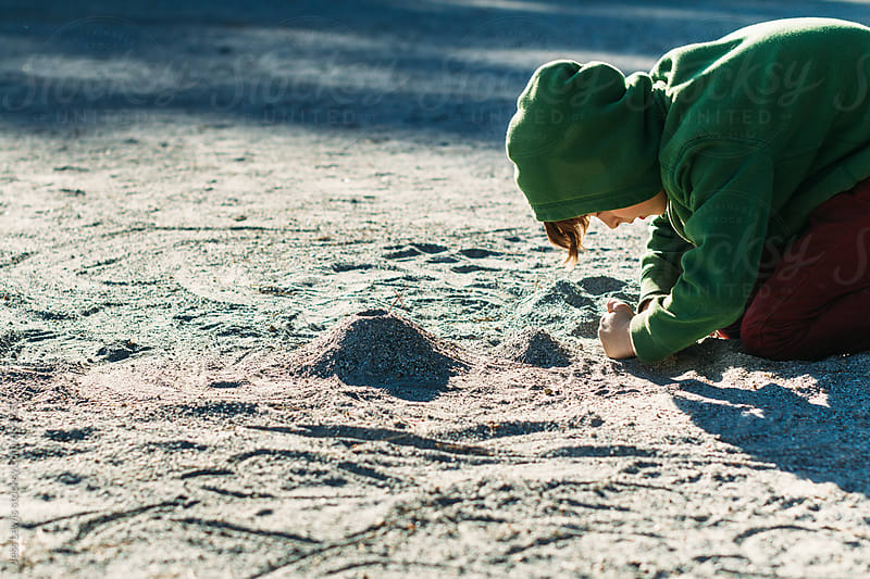 boy playing in the dirt by Jess Lewis for Stocksy United
