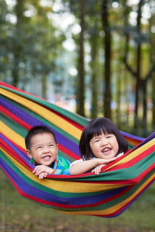 two lovely kids in hammock by Bo Bo for Stocksy United