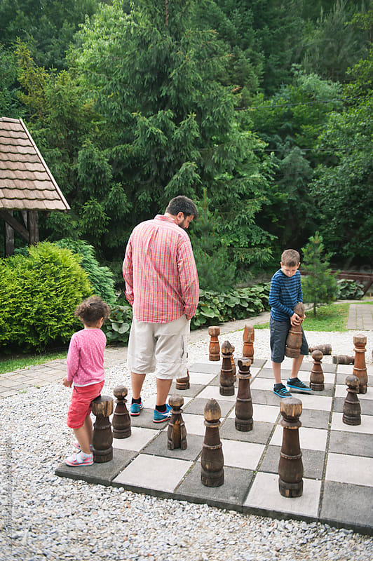 Family playing chess on a giant board outdoors by Lea Csontos for Stocksy United