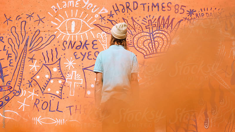 Look from behande  hip young man in front of the orange wall with smoke bomb. by Audrey Shtecinjo for Stocksy United