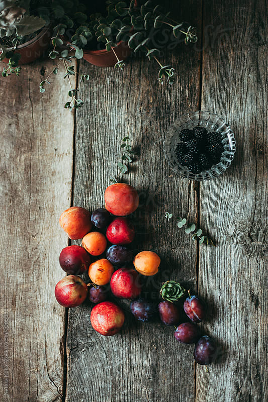 Various colorful summer fruit on a wooden background by Natasa Kukic for Stocksy United