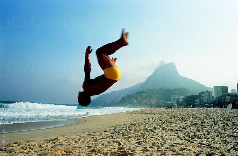 Man back flipping on beach. Ipanema. Rio de Janeiro. Brazil by Hugh Sitton for Stocksy United
