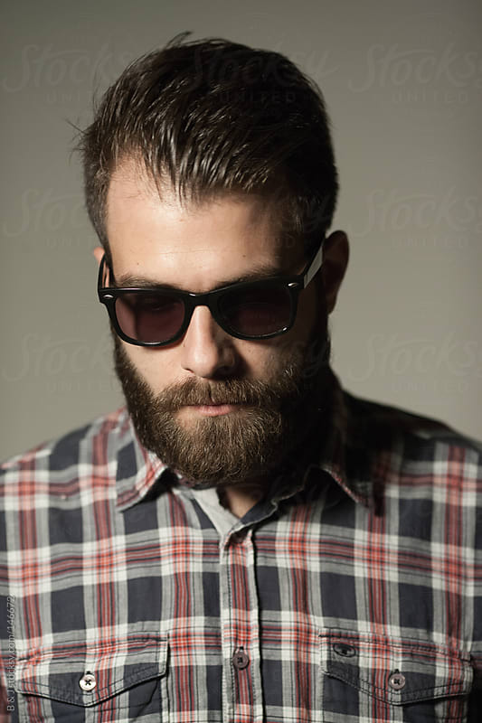portrait of ma young man with a beard by B & J for Stocksy United