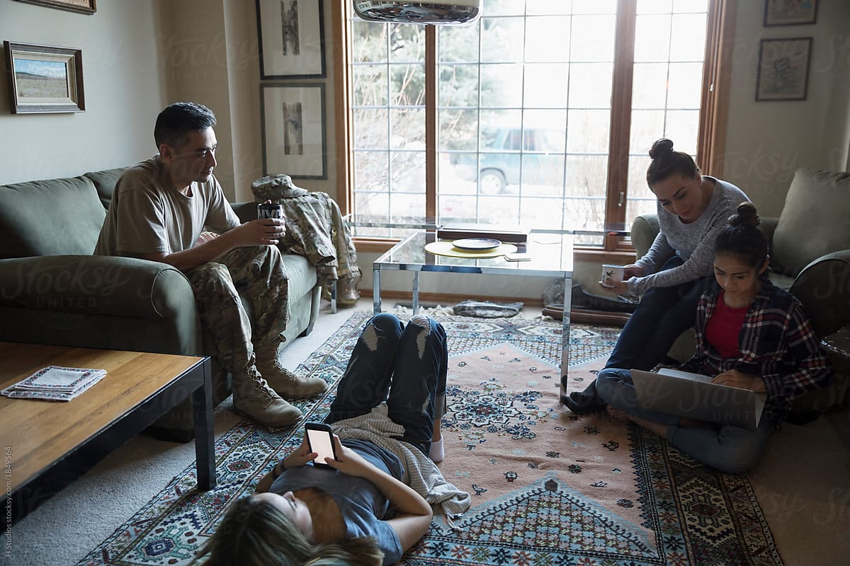 Soldier and family relaxing in living room by H Studios ...