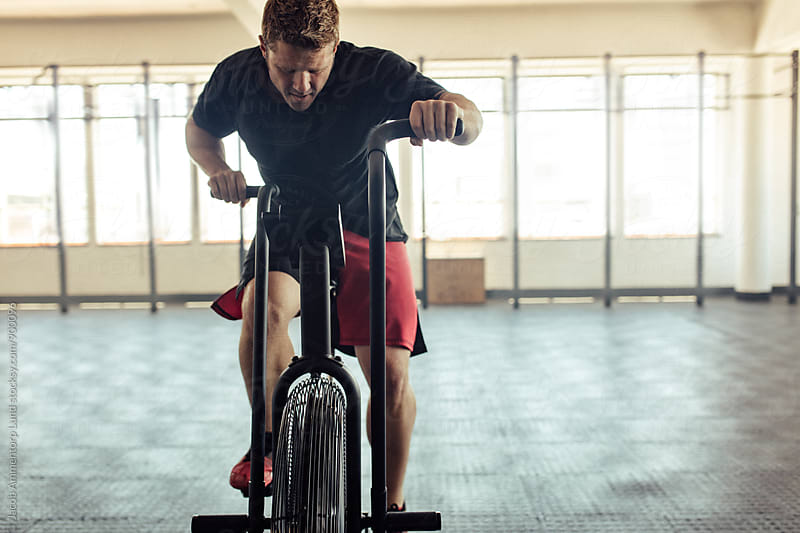 Fit young man using air bike for cardio workout at gym by Jacob Lund for Stocksy United