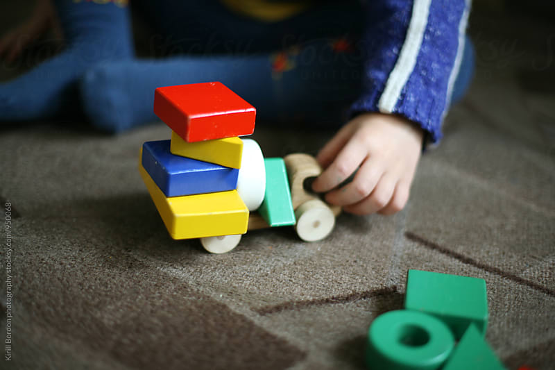 child playing with wooden toys by Kirill Bordon photography for Stocksy United