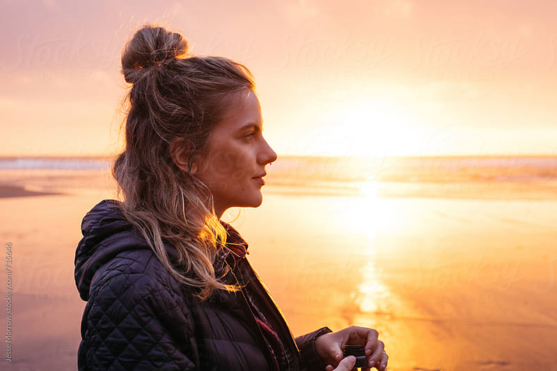 side profile portrait of young woman at sunset on beach by Jesse Morrow for Stocksy United