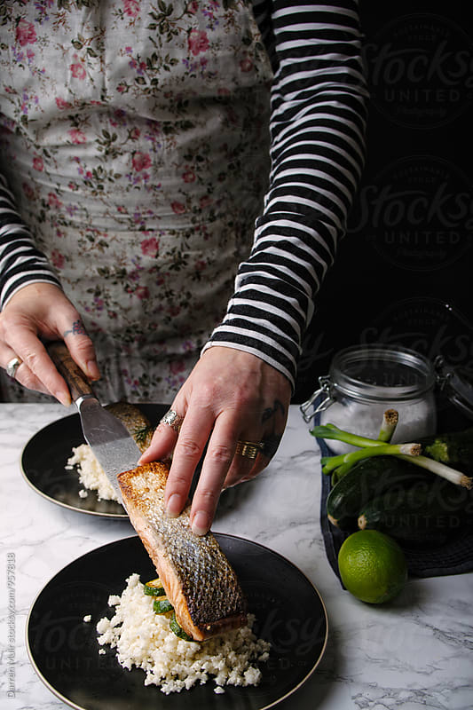 Woman preparing a salmon meal: Woman placing a piece of roasted salmon onto cauliflower couscous. by Darren Muir for Stocksy United