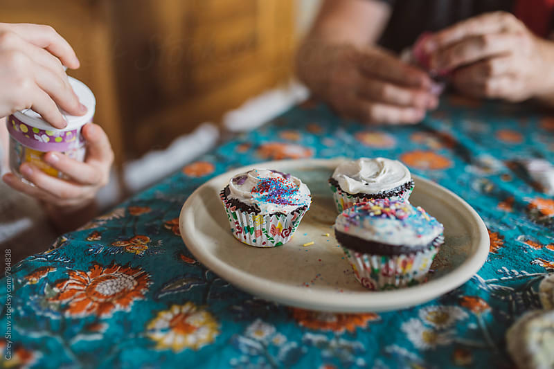 Closeup of father and daughter decorating cupcakes by Carey Shaw for Stocksy United