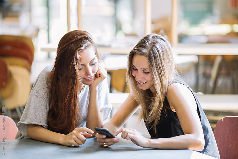 Young caucasian girls watching at the smartphone at the bar by Alberto Bogo for Stocksy United