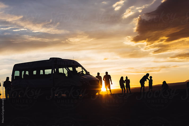 Silhouette of a group of Travellers enjoying sunset by Mauro Grigollo for Stocksy United