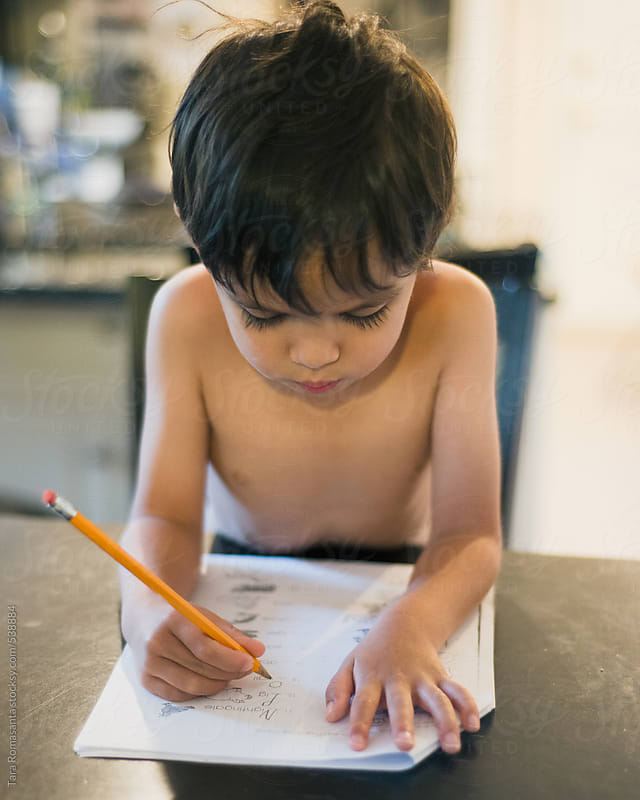 little boy doing homework with a pencil by Tara Romasanta for Stocksy United