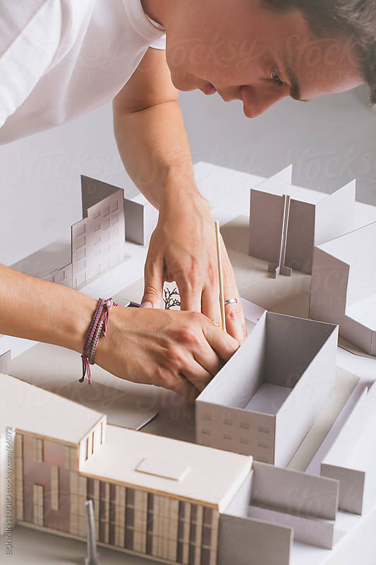 Close up of young architect working on a building project with a scale model.  by BONNINSTUDIO for Stocksy United
