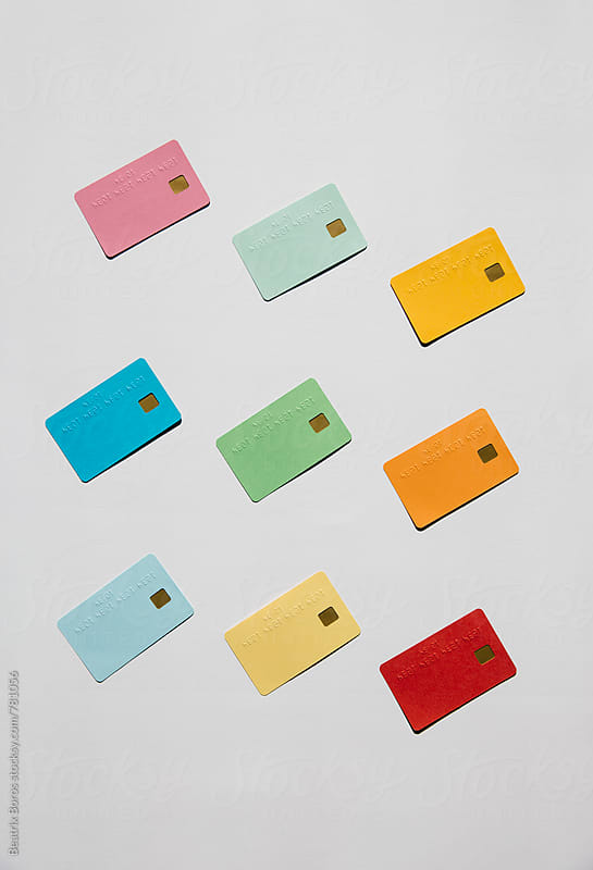 Various debit cards on white background by Beatrix Boros for Stocksy United