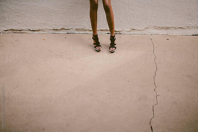 Legs of a black girl in black and white heels  by Gabrielle Lutze for Stocksy United