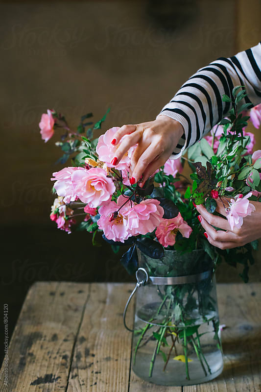 Woman arranging fresh roses. by Alberto Bogo for Stocksy United