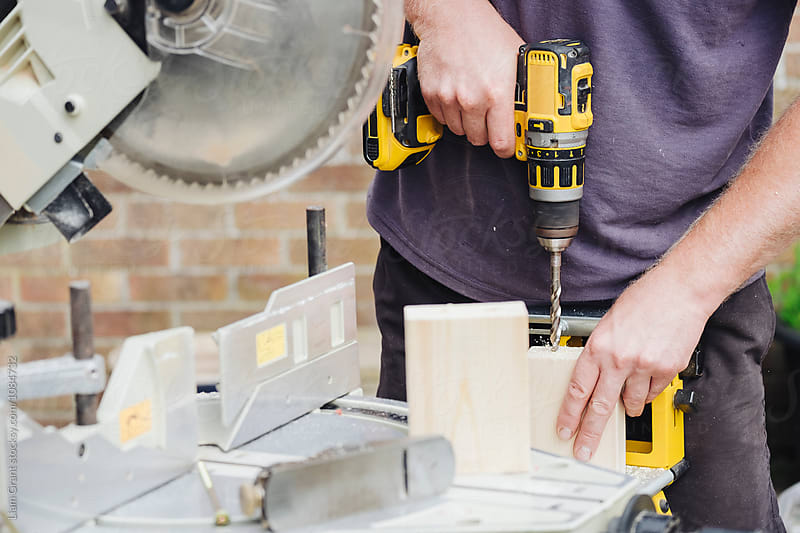Carpenter drilling holes into a piece of wood. UK. by Liam Grant for Stocksy United