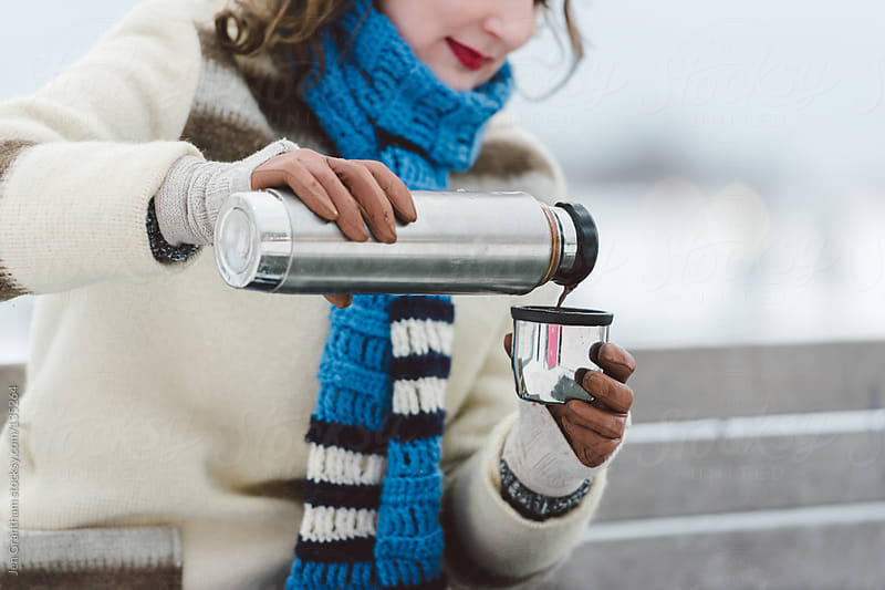 Woman pouring hot chocolate from vacuum flask by Jen Grantham for Stocksy United
