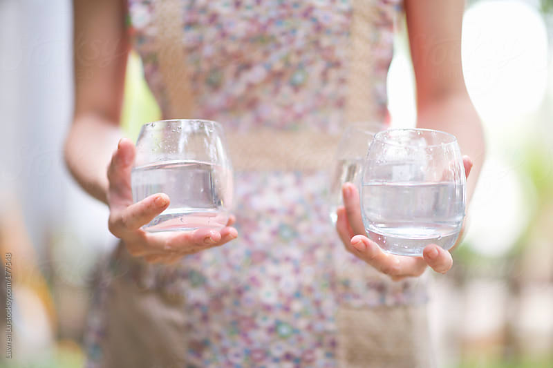 Waitress holding two glasses of water by Lawren Lu for Stocksy United