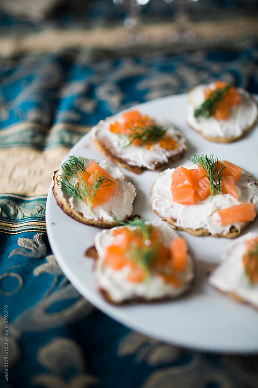Dish of handmade blinies with smoked salmon and caviar on plate on furnished table. by Laura Stolfi for Stocksy United