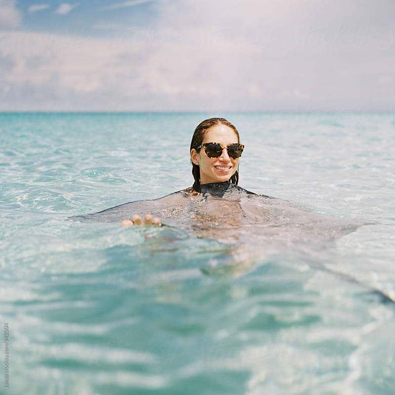 Beautiful woman hugging a stingray in the ocean by Jakob for Stocksy United